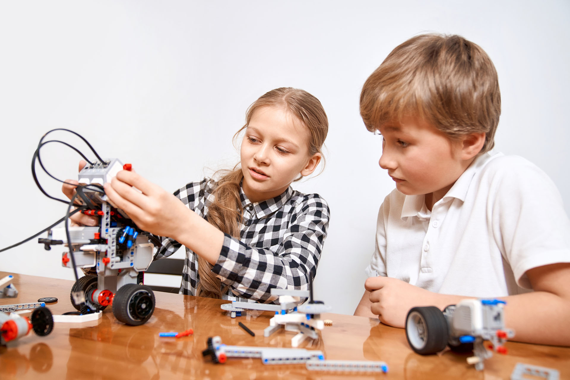 Front,View,Of,Boy,Helping,Girl,In,Creating,Robot,Using